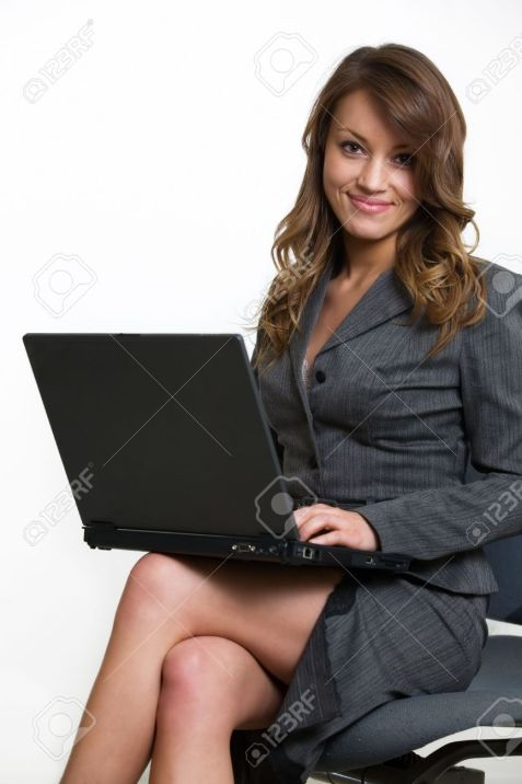1164843-Attractive-brunette-smiling-business-woman-sitting-on-a-chair-wearing-business-suit-while-typing-on--Stock-Photo