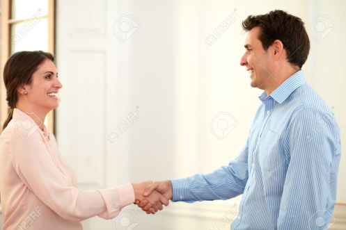 Professional man and woman giving hands greeting